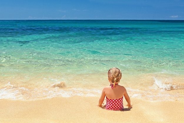 Mädchen im roten badeanzug, der am sandstrandrand sitzt