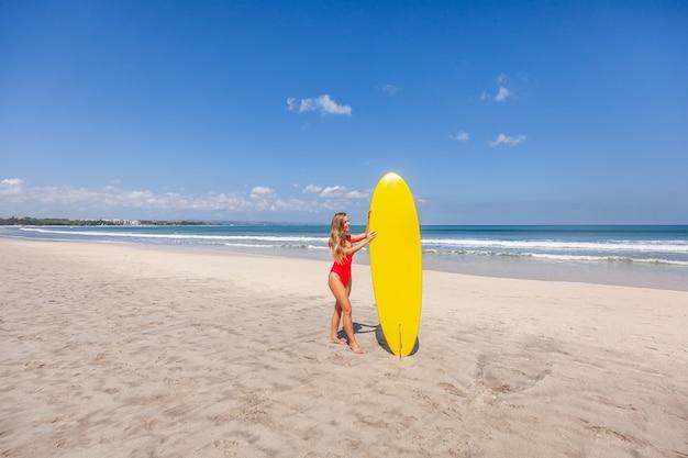 Mädchen im roten badeanzug, der das surfbrett allein steht auf dem strand hält