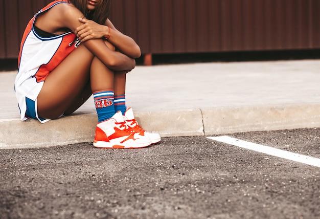 Mädchen im roten basketball trägt die kleidung zur schau, die auf asphalt sitzt