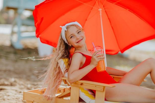 Mädchen im roten bikini, der auf einem strandstuhl mit rotem regenschirm liegt und einen cocktail genießt