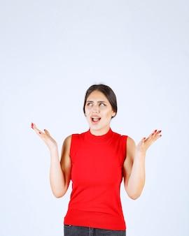 Mädchen im roten hemd, das auf beide seiten zeigt.