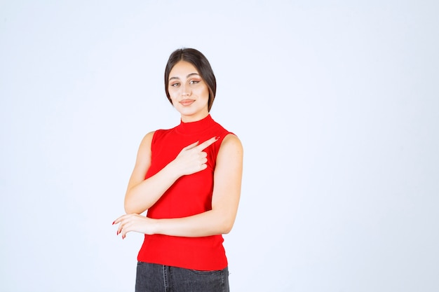 Mädchen im roten hemd, das auf die rechte seite zeigt.
