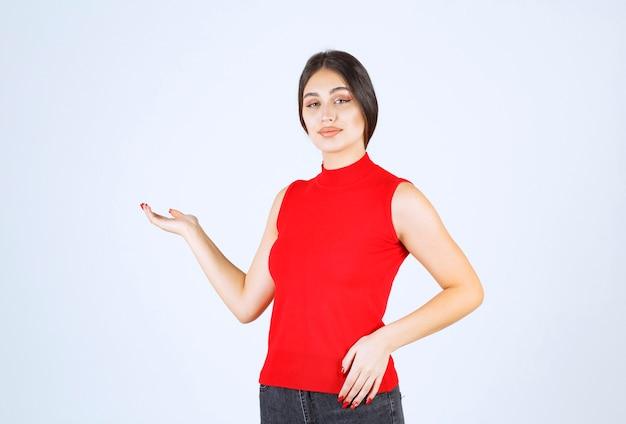 Mädchen im roten hemd, das auf etwas links zeigt.