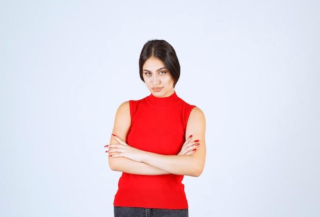 Mädchen im roten hemd, das denkt und analysiert.