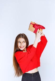 Mädchen im roten hemd, das die geschenkbox mit rotem band schüttelt, um zu erraten, was drin ist.