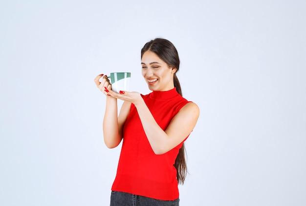 Mädchen im roten hemd, das eine kaffeetasse hält.