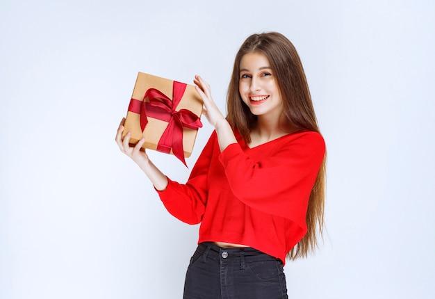 Mädchen im roten hemd, das eine pappgeschenkbox hält, die mit rotem band umwickelt wird.