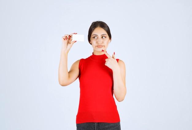 Mädchen im roten hemd, das eine visitenkarte hält und verwirrt und unzufrieden aussieht.