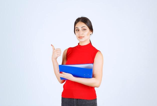 Mädchen im roten hemd, das einen blauen geschäftsordner hält.