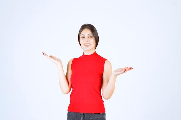 Mädchen im roten hemd, das etwas in ihrer offenen hand zeigt.