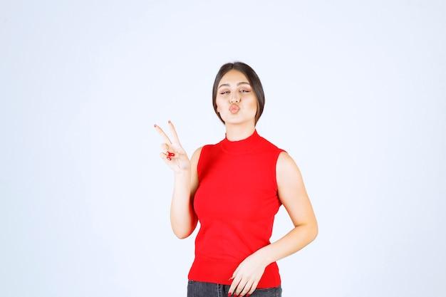 Mädchen im roten hemd, das friedens- und freundschaftszeichen zeigt.