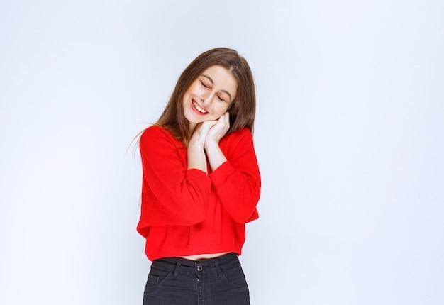 Mädchen im roten hemd, das hände mit fröhlichem gesicht vereint.