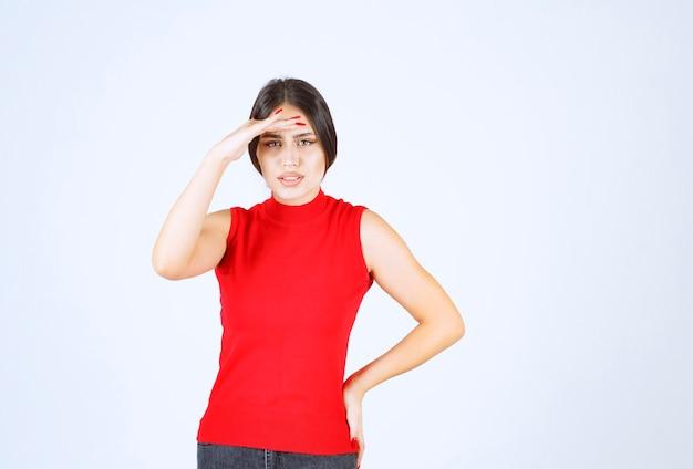 Mädchen im roten hemd, das hand an ihre stirn legt und vorwärts schaut.