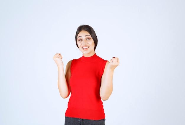 Mädchen im roten hemd, das ihre armmuskeln und fäuste zeigt.