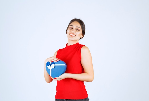 Mädchen im roten hemd, das ihre blaue herzform-geschenkbox darstellt.