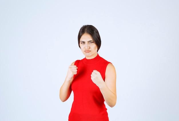 Mädchen im roten hemd, das ihre fäuste und macht zeigt.