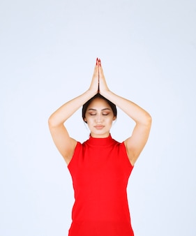 Mädchen im roten hemd, das ihre hände vereint und betet.