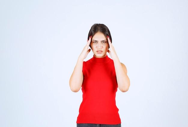 Mädchen im roten hemd, das ihren verstand denkt und auffrischt.