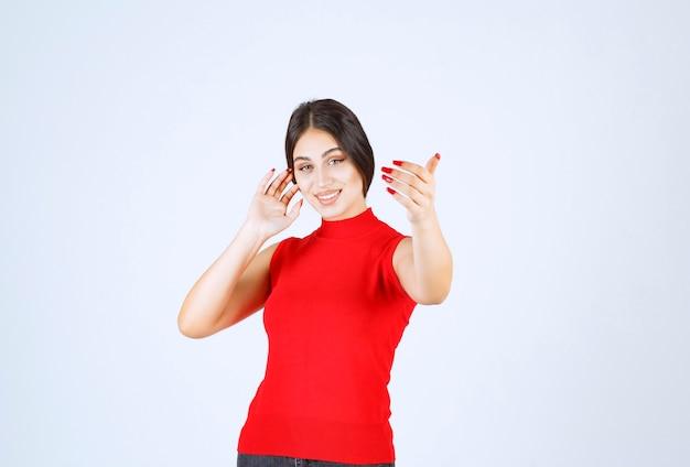 Mädchen im roten hemd, das jemanden grüßt oder einlädt.
