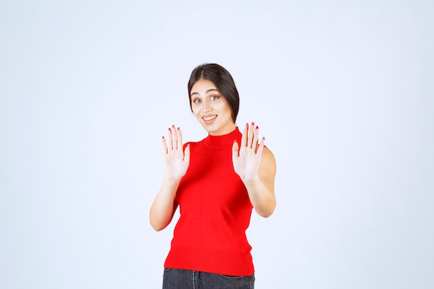 Mädchen im roten hemd, das jemanden stoppt.
