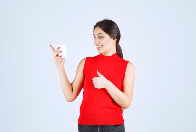 Mädchen im roten hemd, das kaffee trinkt und positives zeichen zeigt.