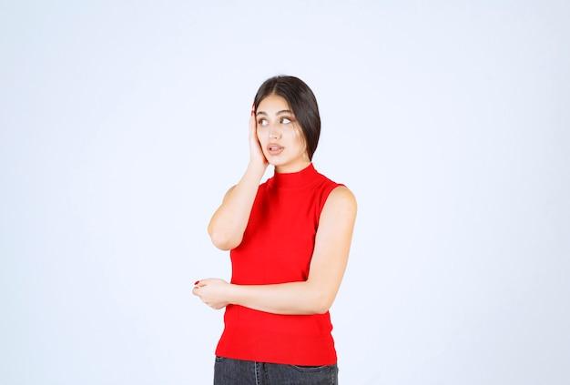 Mädchen im roten hemd, das nerviges und langweiliges gesicht macht.
