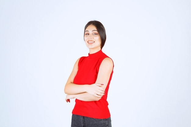 Mädchen im roten hemd, das neutrale, positive und ansprechende posen gibt.