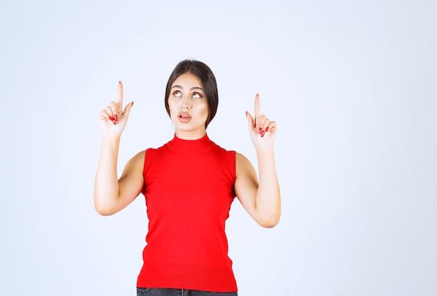 Mädchen im roten hemd, das oben zeigt.