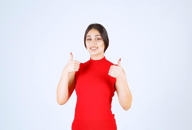 Mädchen im roten hemd, das sich daumen zeigt.