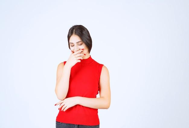 Mädchen im roten hemd, das wegen schlechten geruchs den atem anhält.