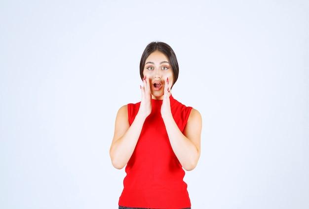 Mädchen im roten hemd sieht von etwas unerwartetem überrascht aus.