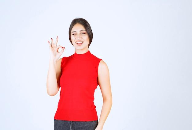 Mädchen im roten hemd winkt und zeigt ihre zufriedenheit.