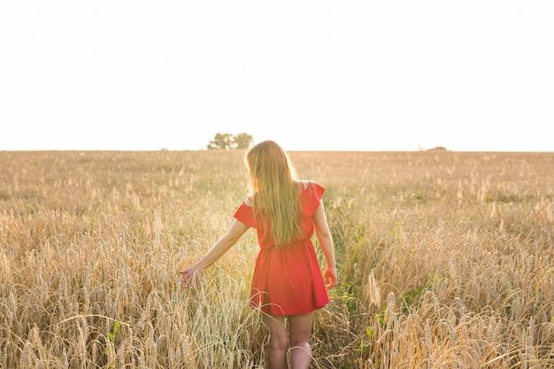 Mädchen im roten kleid auf dem feld. rückansicht