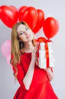 Mädchen im roten kleid hält kästen mit geschenken