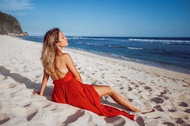 Mädchen im roten kleid sitzt auf weißem sand