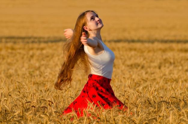 Mädchen im roten rock, der in den weizenfeldarmen wirbelt, breitete sich aus