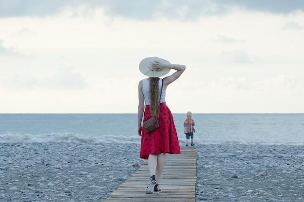 Mädchen im roten rock und im hut gehend entlang die plattform zum meer, sonnenuntergang. blick von hinten