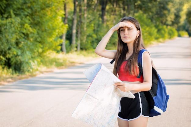 Mädchen im roten t-shirt und in den schwarzen kurzen hosen mit dem rucksack, der weg schaut, während er seine hand nahe stirn hält, um sich vor den sonnenstrahlen zu schützen und versucht, richtige richtung zu finden