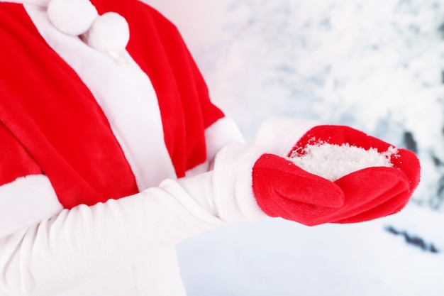 Mädchen im roten weihnachtsumhang und in den handschuhen, auf winterhintergrund