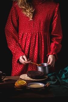 Mädchen im roten weinlesekleid bereitet einen schokoladenkuchen mit kirschen vor