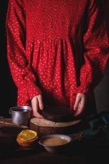 Mädchen im roten weinlesekleid bereitet einen schokoladenkuchen mit kirschen vor.