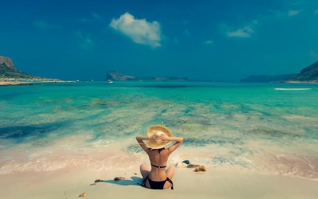 Mädchen im schwarzen bikini und mit hut am strand von balos