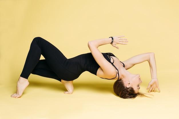 Mädchen im schwarzen, das übung vom yoga am gelb tut.