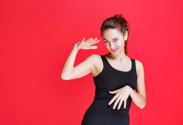 Mädchen im schwarzen hemd, das die abmessungen eines objekts zeigt. foto in hoher qualität
