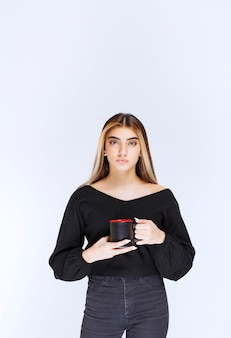 Mädchen im schwarzen hemd, das eine schwarze kaffeetasse hält. foto in hoher qualität