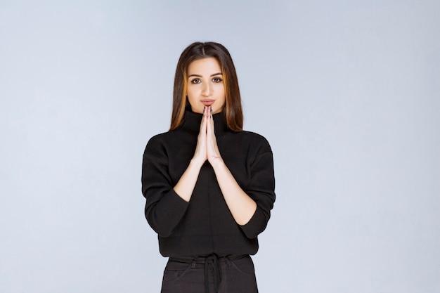 Mädchen im schwarzen hemd, das ihre hände vereint und betet. foto in hoher qualität