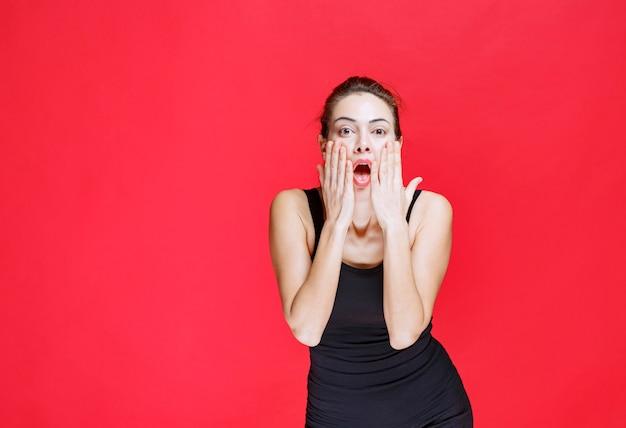 Mädchen im schwarzen hemd, das ihren kopf hält und als dummkopf reagiert. foto in hoher qualität