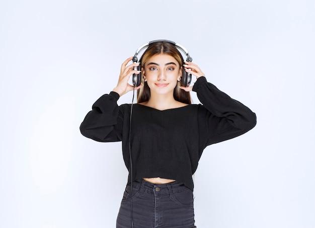 Mädchen im schwarzen hemd, das kopfhörer trägt und musik hört. foto in hoher qualität