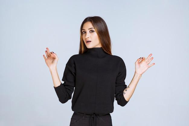 Mädchen im schwarzen hemd, das positives handzeichen zeigt. foto in hoher qualität
