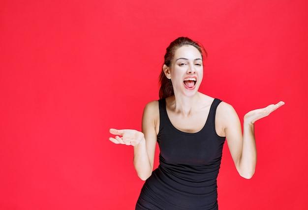 Mädchen im schwarzen hemd, das wie ein dummkopf laut lacht. foto in hoher qualität